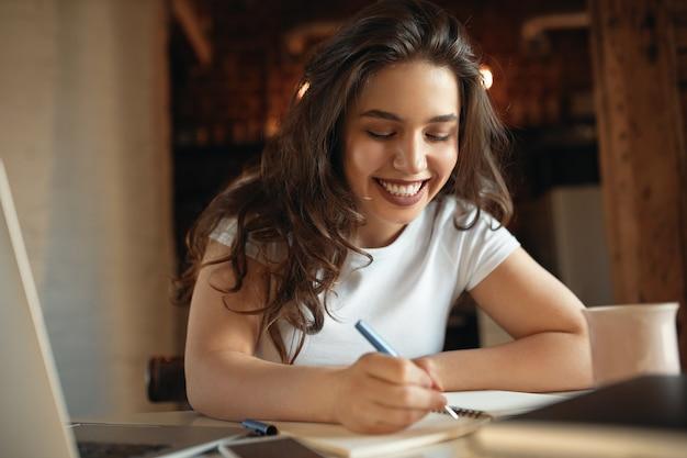 Schönes studentenmädchen mit molligen wangen, die stifthandschrift im notizbuch halten, während entfernt von zu hause lernen
