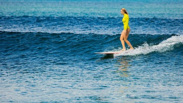 Schönes surfermädchen reitet ein longboard und macht einen nasenritttrick.