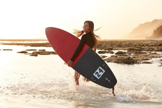 Schönes surfmädchen hat aktiven lebensstil, trägt surfbrett, sieht glücklich aus
