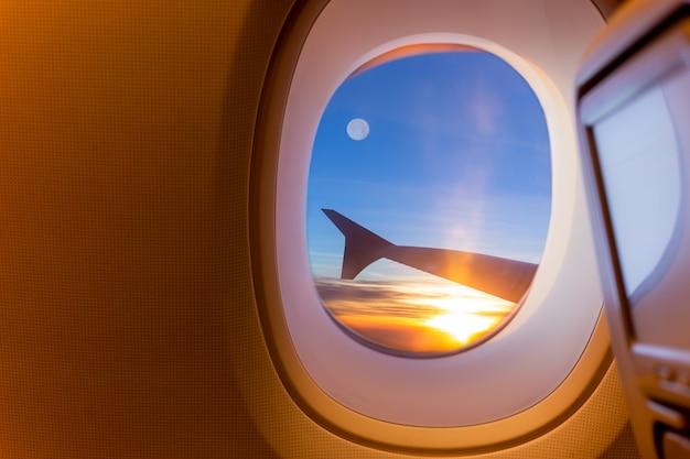 Schönes szenisches des sonnenaufgangs und des vollmonds durch das flugzeugfenster.