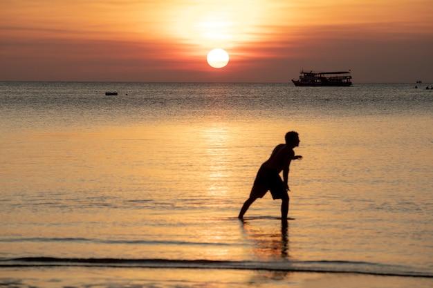 Schönes szenisches des sonnenunterganghimmels und -leute, die auf strand sich entspannen