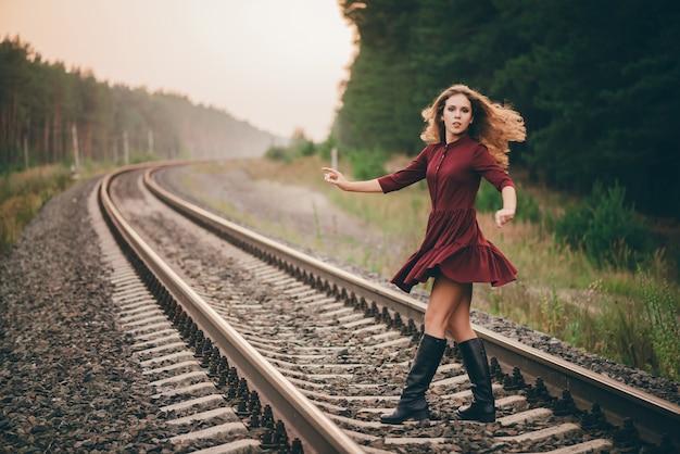 Schönes tanzendes mädchen mit lockigem natürlichem haar genießen natur im wald auf eisenbahn. träumerin im burgunderfarbenen kleid auf der eisenbahn spazieren.