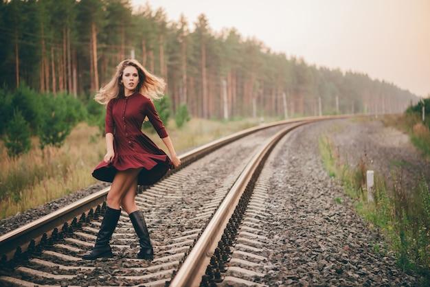 Schönes tanzendes mädchen mit lockigem natürlichem haar genießen natur im wald auf eisenbahn.