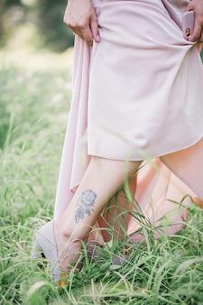 Schönes tattoo in form eines traumfängers auf einem frauenbein