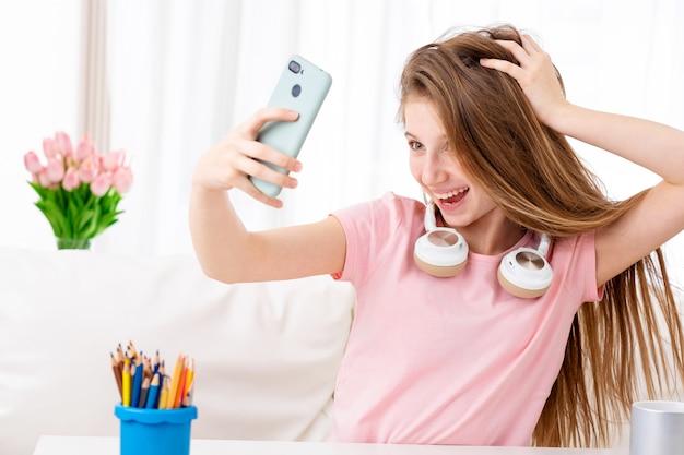 Schönes teen macht selfie aus sich selbst in coolen kopfhörern