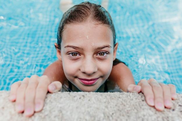 Schönes teenager-mädchen, das in einem pool schwimmt und die kamera betrachtet. spaß und sommerlicher lebensstil