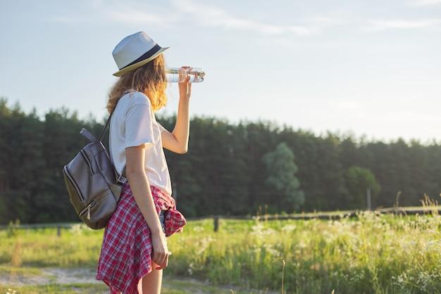 Schönes teenager-mädchen im hut mit rucksackflasche des frischen wassers
