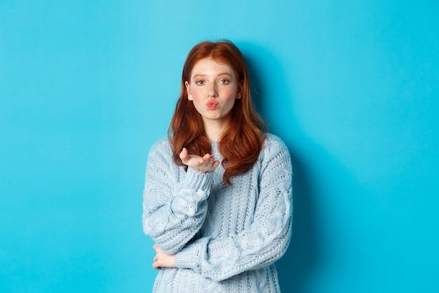 Schönes teenager-mädchen im pullover, der luftkuss bläst, die lippen kräuselt und in die kamera starrt, vor blauem hintergrund stehend
