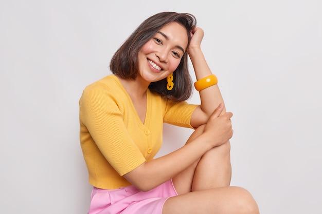 Schönes teenager-mädchen mit östlichem aussehen lehnt sich an die hand und lächelt angenehm, trägt einen gelben pullover, einen rosa rock schaut nach vorne mit süßem gesichtsausdruck sieht sinnlich aus, isoliert über weißer wand