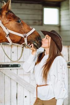 Schönes teenagermädchen im braunen kleid und im braunen pferd, das nahe der tür des holzhauses steht.