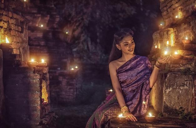 Schönes thailändisches mädchen im thailändischen traditionellen kostüm mit kerze nachts