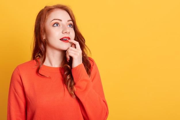 Schönes trendiges mädchen im orangefarbenen pullover, der tief in gedanken ist