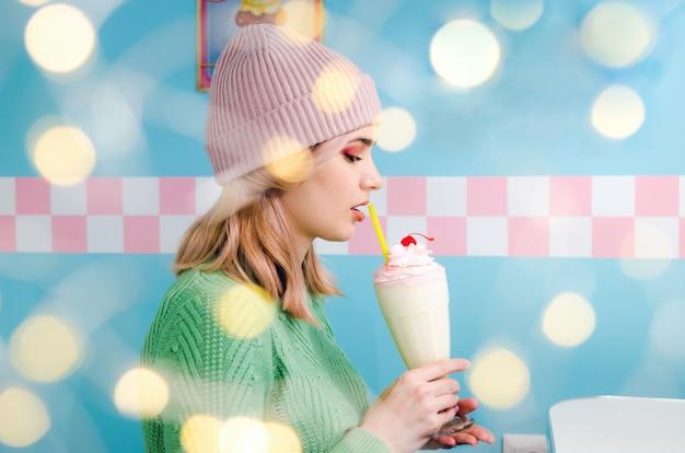 Schönes trinkendes vanillemilchshake des jungen mädchens im café