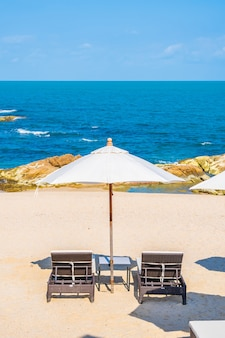 Schönes tropisches strandmeer mit regenschirm und stuhl um weiße wolke und blauen himmel für urlaubsreisen