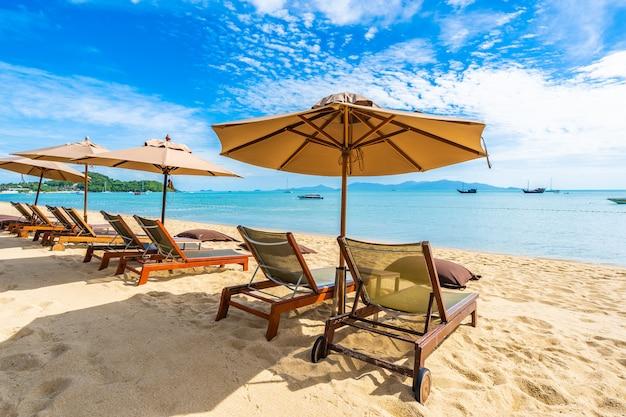 Schönes tropisches strandmeer und -ozean mit kokosnusspalme und regenschirm und stuhl auf blauem himmel