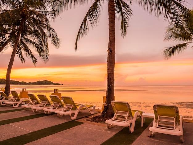 Schönes tropisches strandmeer und -ozean mit kokosnusspalme zur sonnenaufgangzeit