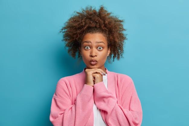 Schönes überraschtes afroamerikanisches junges mädchen hat buschiges lockiges dunkles haar hält hände unter kinn und lippen gerundet