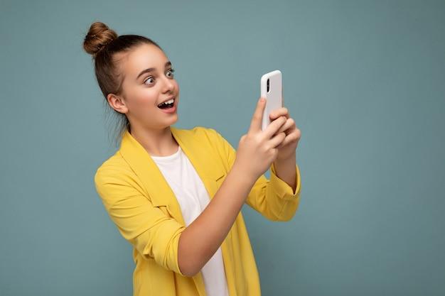 Schönes überraschtes junges mädchen mit gelber jacke und weißem t-shirt, das isoliert auf blauem hintergrund steht und per telefon im internet surft und auf den mobilen bildschirm schaut