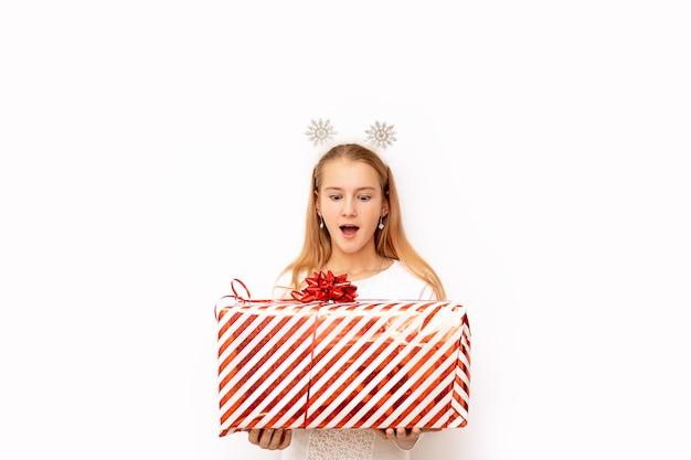Schönes überraschtes kindermädchen, das eine rot gestreifte weihnachtsgeschenkbox mit einem band und einer schleife in ihren händen hält. es gibt schneeflocken auf dem kopf. isoliert