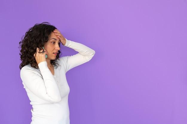 Schönes überraschtes mädchen, das am telefon lokalisiert über lila hintergrund spricht. hand auf ihre stirn. speicherplatz kopieren. weißes hemd und lockiges haar.