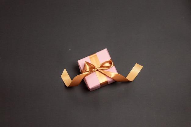 Schönes überraschungsgeschenk eingewickelt im rosa papier mit einem goldbandbogen auf einem dunklen hintergrund.