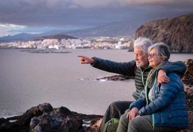 Schönes umarmtes seniorenpaar, das an einem wintertag auf der klippe sitzt und den sonnenuntergang über dem meer genießt. neue junge leute genießen freiheit und ruhestand. bewölkter himmel, küste und berge im hintergrund