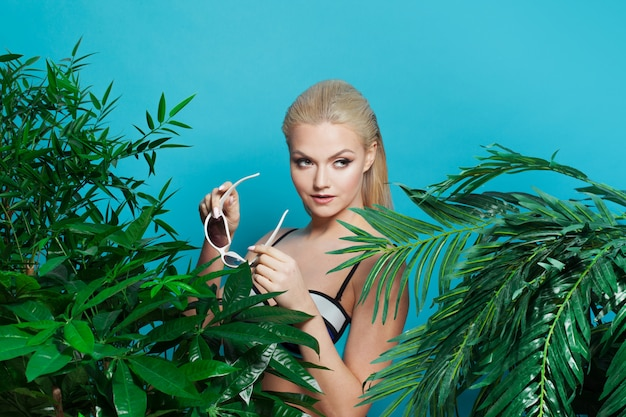 Schönes und charmantes blondes mädchen mit sonnenbrille zwischen palmen und tropischen pflanzen.