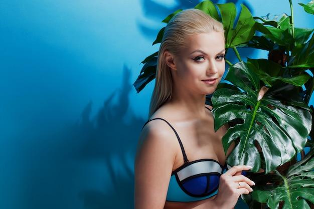 Schönes und charmantes blondes mädchen unter palmen und tropischen pflanzen. glück, ruhe auf dem meer