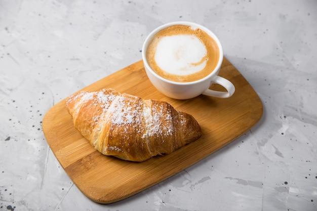 Schönes und einfaches traditionelles französisches frühstück mit frischen croissants und einer tasse cappuccino