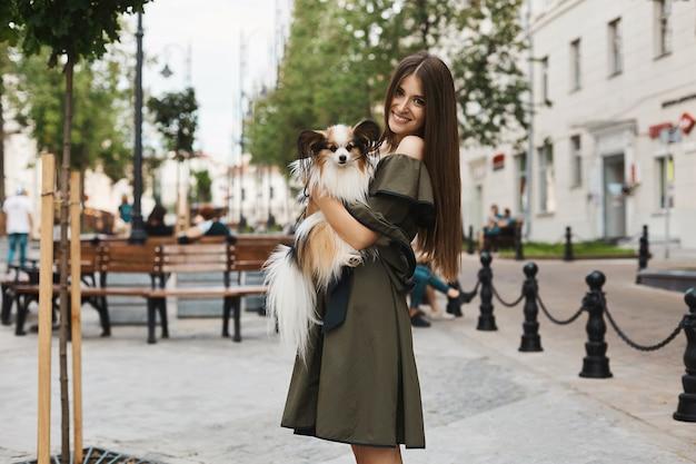 Schönes und fröhliches brünettes modellmädchen mit glänzendem lächeln, im kurzen kleid mit einem kleinen niedlichen papillonhund auf ihren händen, die draußen im alten stadtzentrum aufwerfen
