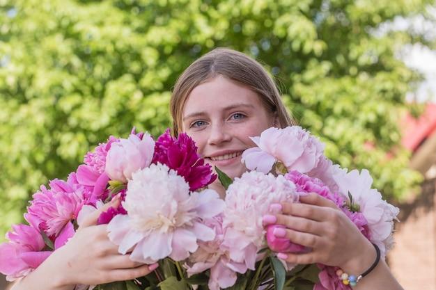 Schönes und glückliches junges mädchen im sommer mit einem schönen strauß pfingstrosen in der natur. nahaufnahme porträt im freien