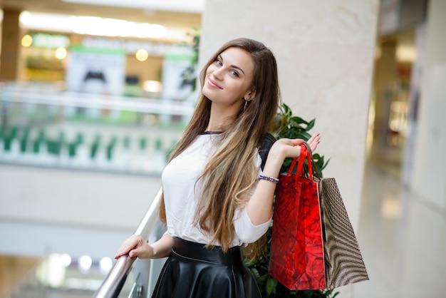 Schönes und glückliches mädchen beim einkaufen im einkaufszentrum.
