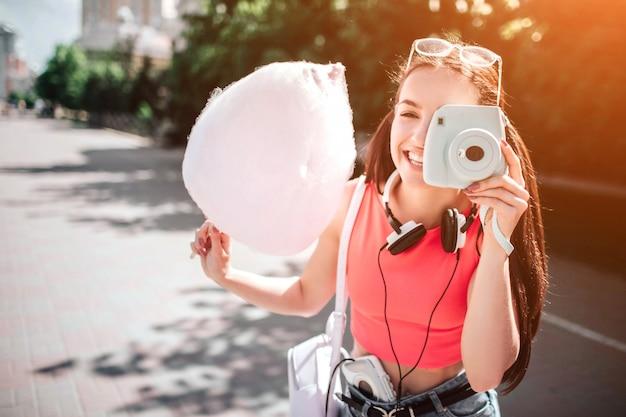 Schönes und herrliches mädchen steht und wirft auf, wie sie foto mit ihrer weißen kamera macht. auch mädchen hält eine zuckerwatte in der hand. es gibt kopfhörer um ihren hals.
