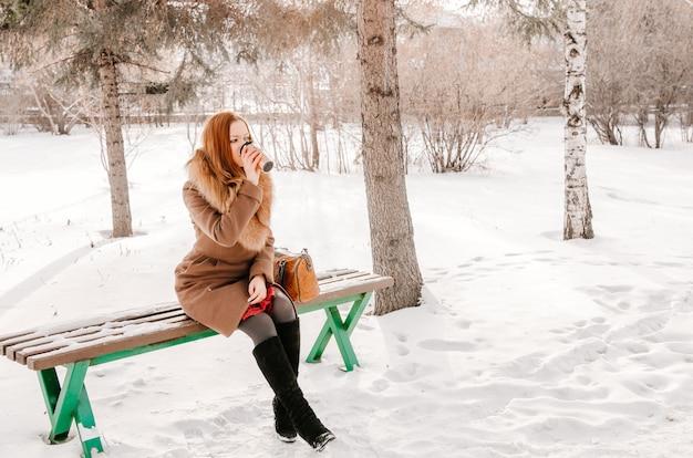 Schönes und junges mädchen in einem mantel, der auf der bank im park sitzt