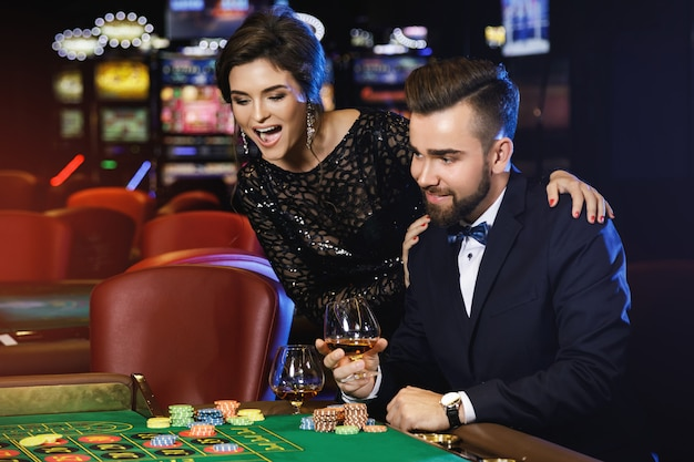 Schönes und reiches paar, das roulette im kasino spielt