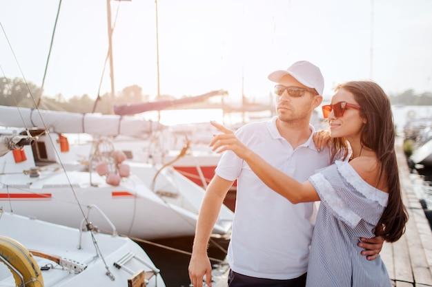 Schönes und selbstbewusstes paar steht auf pier und umarmt sich. sie stehen sehr nah. mädchen zeigen mit dem finger