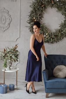 Schönes und sexy model-mädchen mit modischer frisur im dunkelblauen kleid posiert in für weihnachten dekoriertem interieur