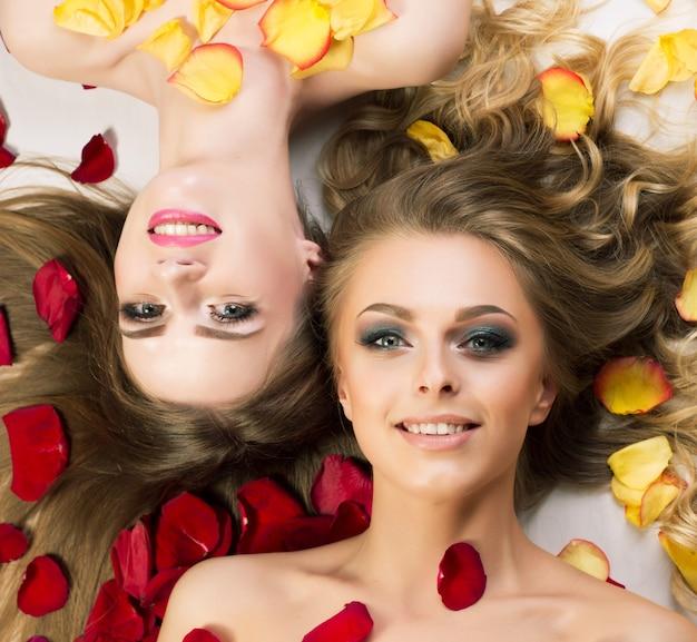 Schönes und sexy modell mit rosenblättern, lokalisiert auf weißem hintergrund.