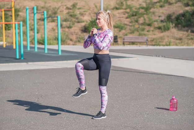 Schönes und sportliches blondes mädchen, das sprünge auf dem straßensportplatz tut