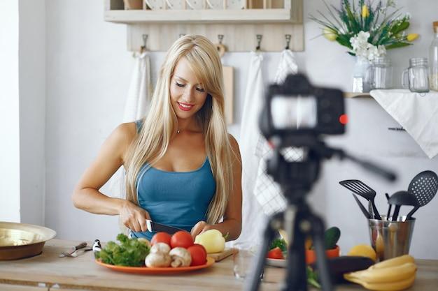 Schönes und sportliches mädchen in einer küche, die ein video notiert