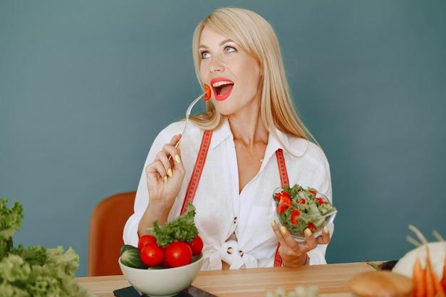 Schönes und sportliches mädchen in einer küche mit einem gemüse