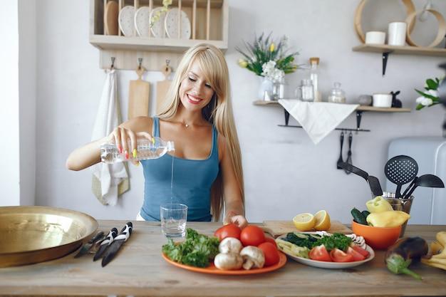 Schönes und sportliches mädchen in einer küche mit gemüse
