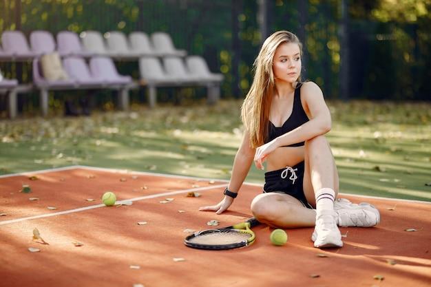 Schönes und stilvolles mädchen auf dem tennisplatz