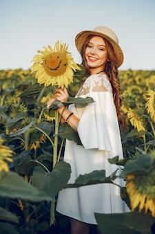 Schönes und stilvolles mädchen auf einem gebiet mit sonnenblumen