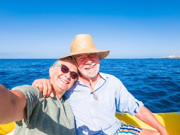 Schönes und süßes paar senioren oder alte leute mitten auf dem meer, die mit einem kleinen boot neue orte fahren und entdecken. reife frau, die ein telefon hält und ein selfie mit hew-ehemann macht