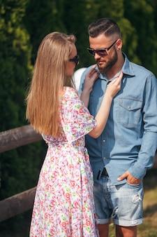 Schönes und zartes mädchen mit blonden haaren, einem hellen kleid und einem blumenstrauß geht in einem sonnigen park mit ihrem hübschen freund in einem blauen hemd und shorts spazieren.
