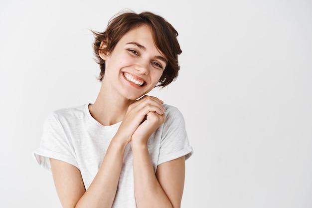 Schönes und zartes mädchen ohne make-up, das lächelt und etwas entzückendes und süßes ansieht, weiße wand