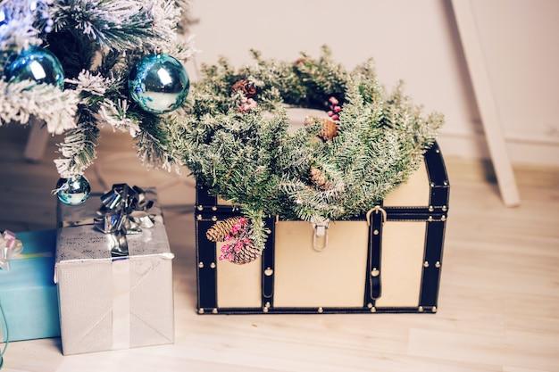 Schönes urlaubsgeschmücktes zimmer mit weihnachtsbaum mit geschenken darunter