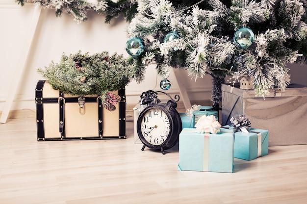 Schönes urlaubsgeschmücktes zimmer mit weihnachtsbaum mit geschenken darunter Premium Fotos