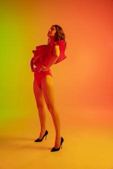 Schönes verführerisches mädchen im modischen roten badeanzug auf hellem grün-orangem hintergrund mit farbverlauf im neonlicht. ganzkörperporträt. exemplar für anzeige. sommer, mode, schönheit, emotionskonzept.